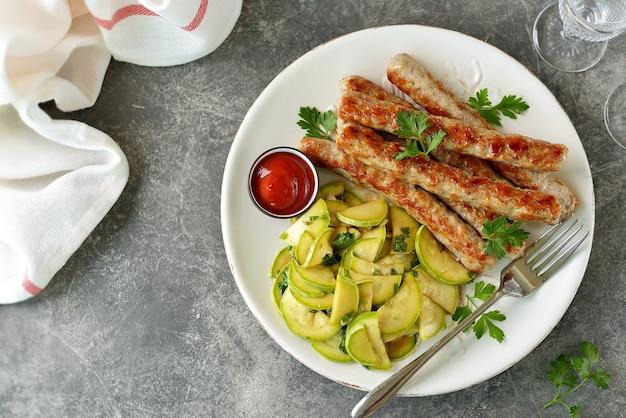 Salsicce di pollo alla griglia con insalata di zucchine