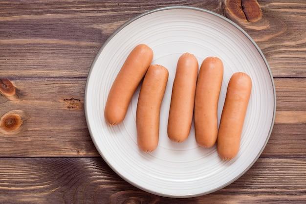 Salsicce di pollo bollite pronte da mangiare su un piatto su un tavolo di legno. vista dall'alto