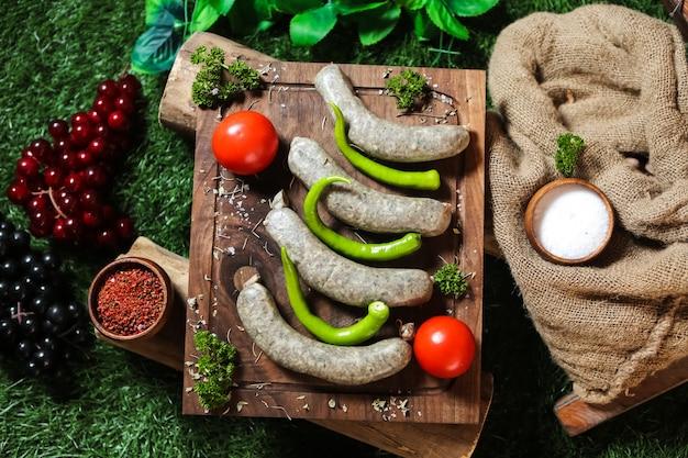 Salsicce fatte in casa sulla tavola di legno pepe pomodoro verdi sale