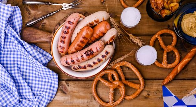Salsicce tedesche tradizionali e brezel di pasticceria per una festa della birra. legno e decorazioni. vista dall'alto