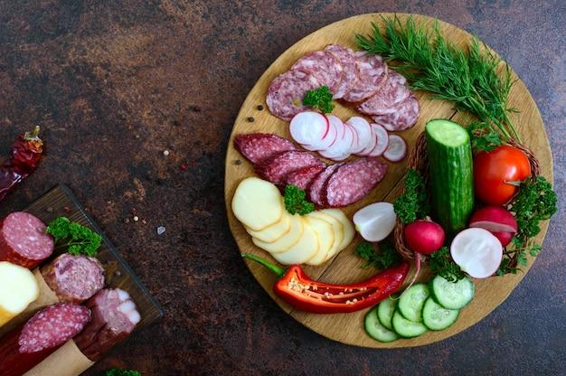 Salsiccia affettata e verdura fresca su un vassoio di legno. vassoio snack. vista dall'alto.