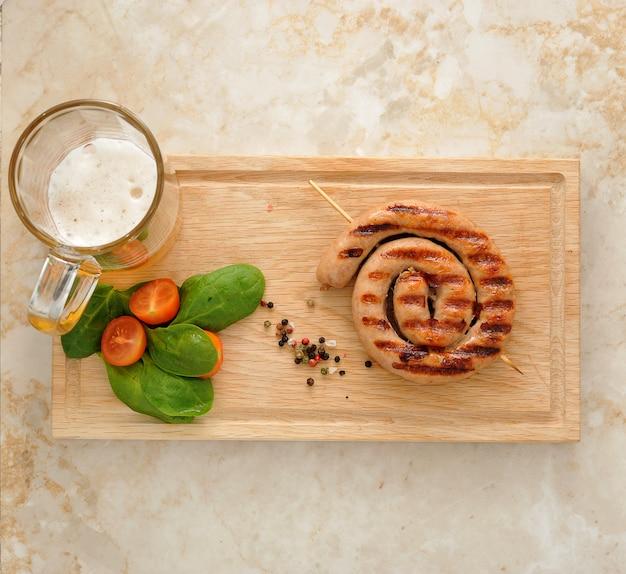 Salsiccia alla griglia a spirale con boccale di birra, spinaci e pomodori