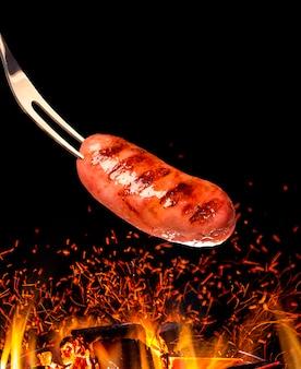 Salsiccia alla griglia alla brace con il fuoco. barbecue brasiliano.