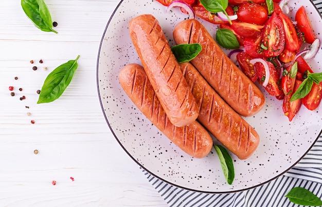 Salsiccia alla griglia con pomodori, basilico e cipolle rosse