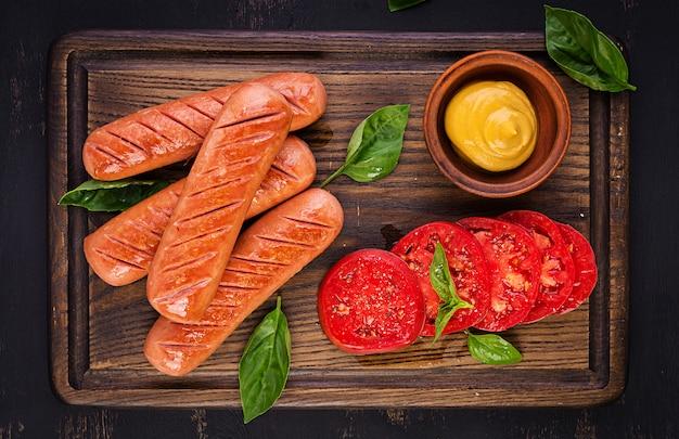 Salsiccia alla griglia con pomodori, insalata di basilico e cipolle rosse. menu barbecue. vista dall'alto
