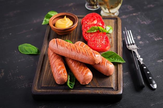 Salsiccia alla griglia con pomodori, insalata di basilico e cipolle rosse. menu barbecue.
