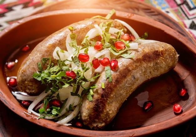 Salsiccia alla griglia in una pentola di terracotta. ristorante georgiano.