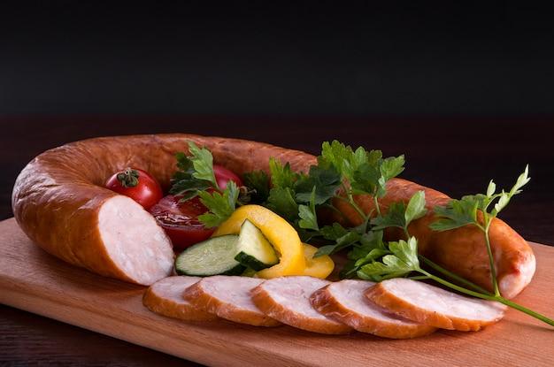 Salsiccia con antipasti in un piatto e su un tagliere.