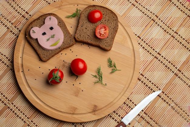 Salsiccia con pane nero e tomates sullo sfondo di legno