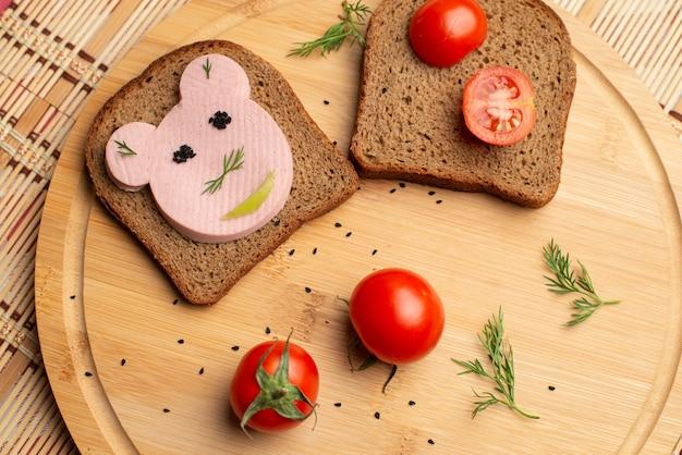 Salsiccia con pane nero e tomates sullo sfondo in legno