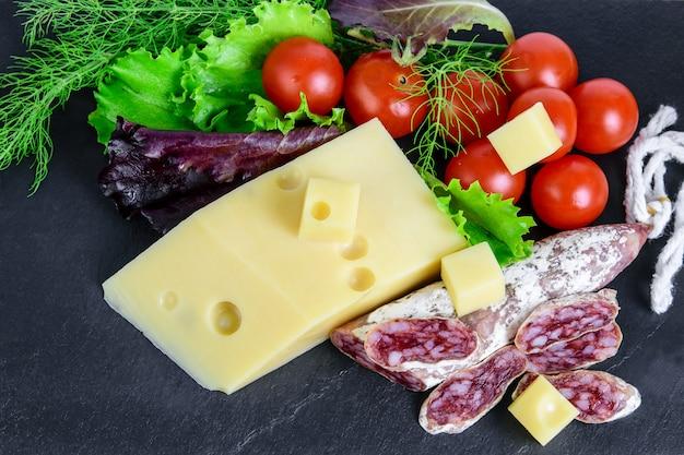 Salsiccia di fuet affettata, formaggio emmental e verdure sul bordo nero delle tapas. cibo veloce e gustoso per merenda.