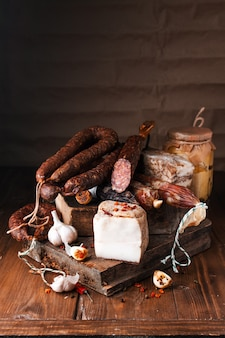 Salsiccia di maiale affumicata. costolette, pane bianco, pane di mais, fagioli, insalata di patate, ecc. varie carni affumicate e barbecue tradizionali. selezione di salumi decorati con aglio e pepe