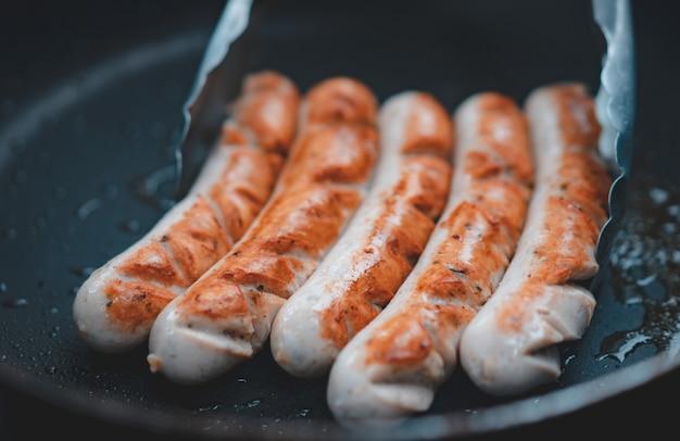 Salsiccia di maiale fatta in casa alla griglia con olio su padella nera