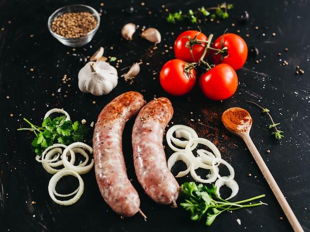 Salsiccia di maiale per marinata e altre spezie: pomodori, prezzemolo, aglio e altri su uno sfondo nero