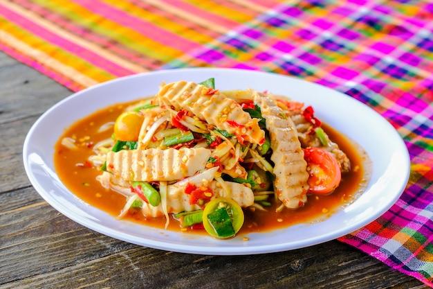Salsiccia di maiale vietnamita som tam (insalata di papaya piccante) con granchio salato, sul tavolo di legno (cibo tailandese)