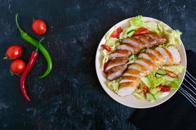 Salsiccia fatta in casa succosa con un'insalata leggera di primavera di verdure fresche su un fondo di legno nero. un piatto tradizionale pasquale. vista dall'alto.