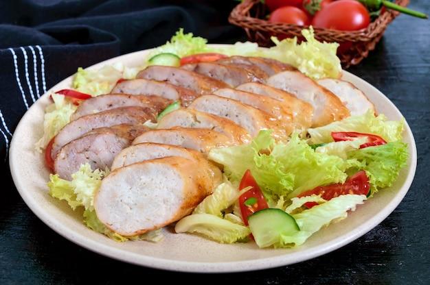 Salsiccia fatta in casa succosa con un'insalata leggera di primavera di verdure fresche su un fondo di legno nero. un piatto tradizionale pasquale.