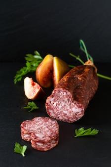 Salsiccia stagionata secca concetto dell'alimento sul bordo nero dell'ardesia