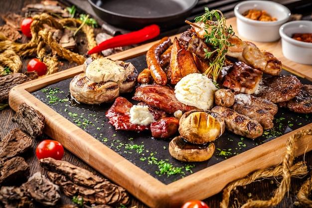 Salsiccie fritte assortite su una griglia su un bordo di legno.