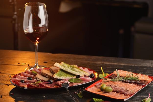 Salsiccie, jamon e prosciutto assortiti con le fette di pane fritto su un piatto rosso. su un tavolo di legno