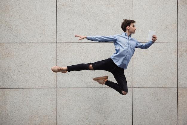 Saltando giovane buinessman davanti agli edifici, in fuga saltando in alto