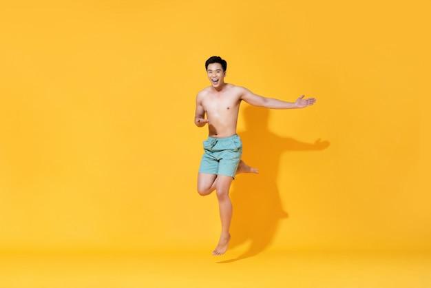Salto asiatico bello senza camicia sorridente energico dell'uomo