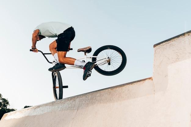 Salto estremo dell'uomo sportivo con la bicicletta