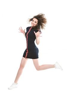Salto sportivo sorridente della donna isolato su una priorità bassa bianca. guardando la fotocamera