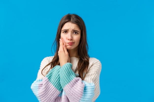 Salute, concetto di stomatologia. donna sciocca e carina in maglione invernale, lamentandosi di mal di denti, con carie o denti cariati, toccando la guancia accigliata e imbronciata dal dolore, aspettando nell'ufficio del dentista