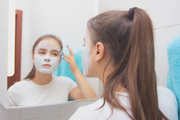 Salute e bellezza. cura della pelle del viso. la ragazza fa una maschera detergente idratante