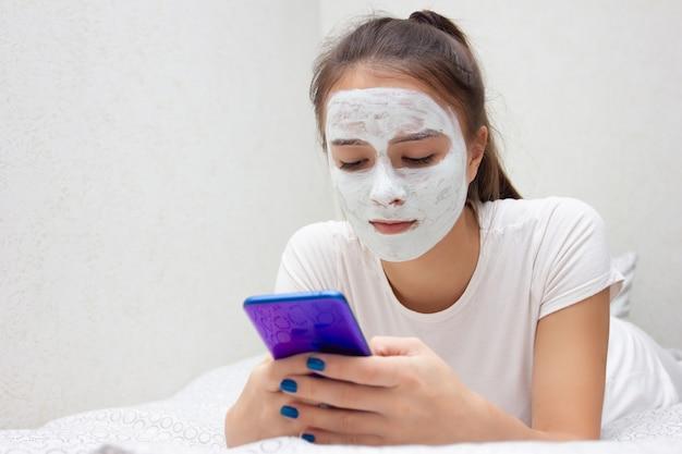 Salute e bellezza. cura della pelle del viso. una ragazza con una maschera idratante sul viso giace con uno smartphone