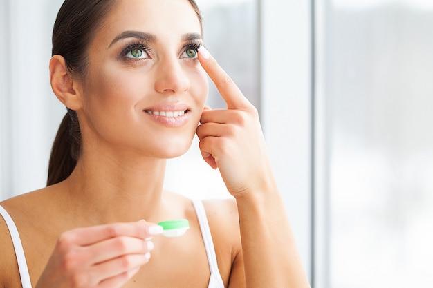 Salute. la ragazza tiene l'obiettivo di contatto in mani. ritratto di una bella donna con gli occhi verdi e lenti a contatto. sguardo sano alta risoluzione