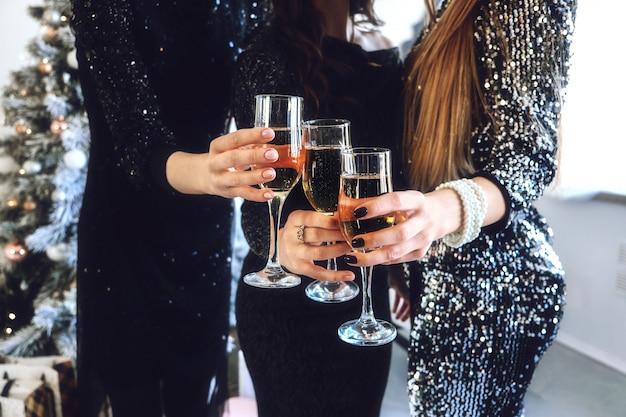 Saluti! primo piano della mano femminile con gli occhiali champagne.