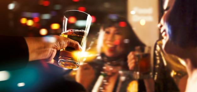 Saluti tintinnio di amici con drink di birra nella notte di festa dopo il lavoro