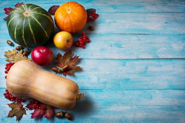 Saluto del ringraziamento con zucche su fondo di legno blu