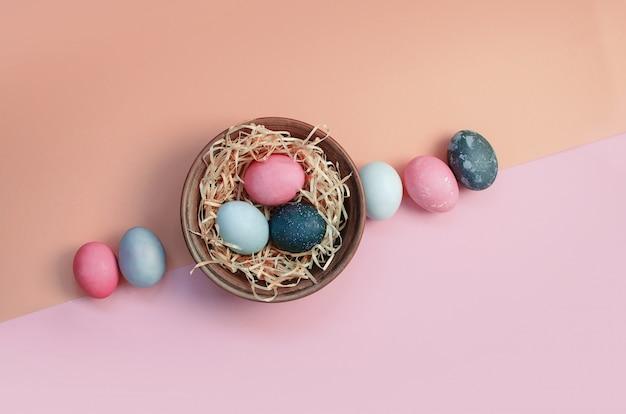 Saluto di pasqua con le uova di pollo multicolori tinte su paglia in zolla