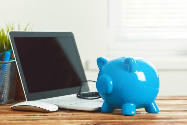 Salvadanaio di porcellino con il computer portatile sulla tavola di legno