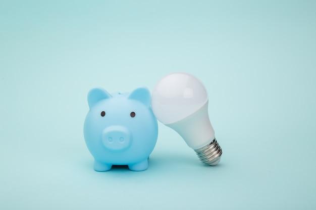 Salvadanaio e lampadina su sfondo blu. concetto di risparmio energetico