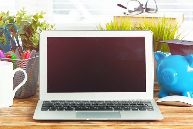 Salvadanaio piggy con il computer portatile sul tavolo di legno