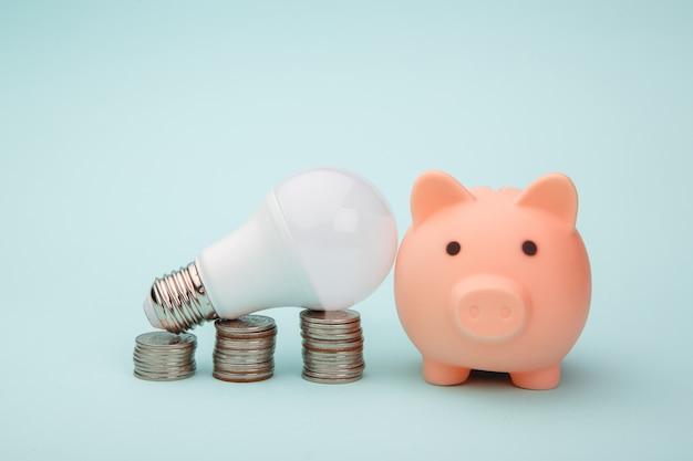 Salvadanaio, pila di monete e lampada a led su sfondo blu. concetto di risparmio energetico