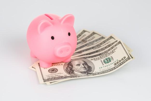 Salvadanaio rosa nel mucchio delle banconote del dollaro, concetto di valuta