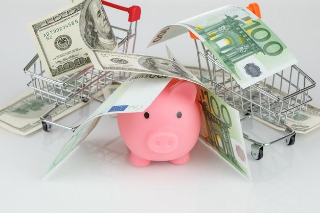 Salvadanaio rosa nel mucchio di banconote in euro e dollaro
