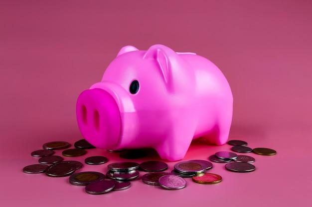 Salvadanaio rosa risparmiare moneta su sfondo rosa