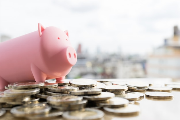Salvadanaio rosa su pile di denaro. concetto di crescita del risparmio in contanti.