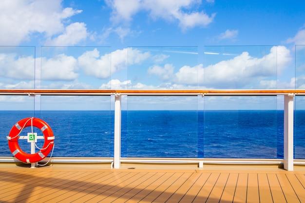 Salvagente arancione su una piattaforma della nave da crociera con l'oceano