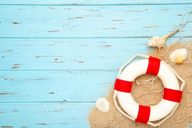 Salvagente bianco rosso con le conchiglie su un fondo di legno