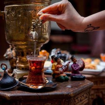 Samovar di vista laterale con bicchiere di tè e figurine e mano umana in tavola sul ristorante