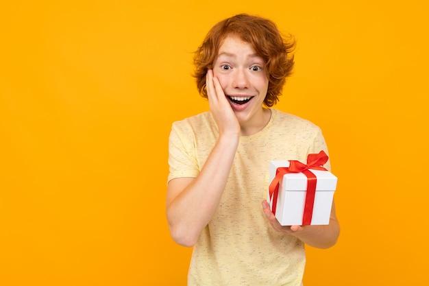 San valentino . adolescente dai capelli rossi sorpreso felice con un regalo in mano su un'arancia