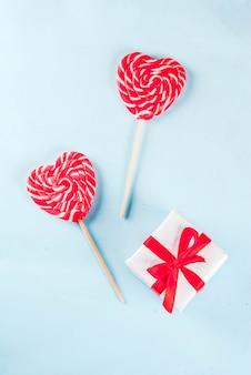 San valentino azzurro, concetto di biglietto di auguri, due lecca-lecca cuore rosso o caramelle dolci su bastoncini, con scatola regalo, copyspace vista dall'alto