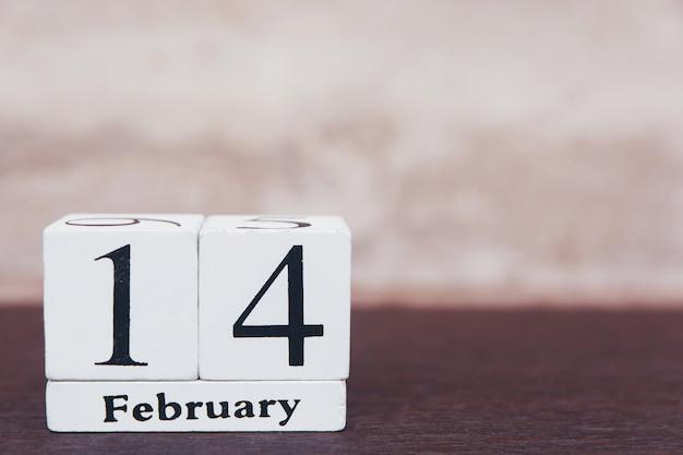 San valentino con il 14 febbraio. calendario di legno del blocco bianco sul fondo di legno della tavola con lo spazio della copia